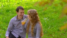 Άνδρας και γυναίκα στο πάρκο, χυμός κατανάλωσης, παιχνίδι, γέλιο φιλμ μικρού μήκους