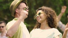 Άνδρας και γυναίκα Flirty νεαρός που αγκαλιάζουν και που απολαμβάνουν τη μουσική χορού στο θερινό κόμμα απόθεμα βίντεο