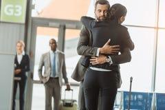 άνδρας που αγκαλιάζει τη γυναίκα στον αερολιμένα κατόπιν στοκ φωτογραφία