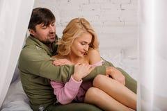 Άνδρας που αγκαλιάζει τη γυναίκα του στο άσπρο κρεβάτι στοκ εικόνα με δικαίωμα ελεύθερης χρήσης