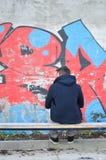 Άνδρας που βλέπει νεαρός από την πλάτη που εξετάζει ένα γκράφιτι Στοκ Εικόνες