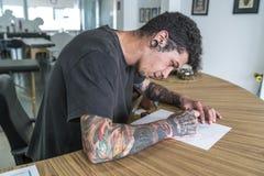 Άνδρας που διαστίζεται νεαρός σχεδιασμός μιας δερματοστιξίας στοκ εικόνες