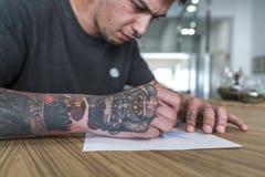 Άνδρας που διαστίζεται νεαρός σχεδιασμός μιας δερματοστιξίας στοκ εικόνες με δικαίωμα ελεύθερης χρήσης