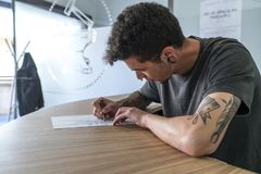 Άνδρας που διαστίζεται νεαρός σχεδιασμός μιας δερματοστιξίας στοκ εικόνα με δικαίωμα ελεύθερης χρήσης