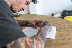 Άνδρας που διαστίζεται νεαρός σχεδιασμός μιας δερματοστιξίας στοκ εικόνα
