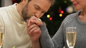 Άνδρας που φιλά tenderly το χέρι γυναικών, ρομαντική ημερομηνία στη νύχτα Χριστουγέννων, κινηματογράφηση σε πρώτο πλάνο φιλμ μικρού μήκους