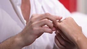 Άνδρας που φορά το δαχτυλίδι αρραβώνων με το διαμάντι στο δάχτυλο της αγαπημένης γυναίκας, κινηματογράφηση σε πρώτο πλάνο απόθεμα βίντεο