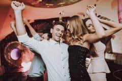 Άνδρας που χορεύει με τη γυναίκα foreground Τραγουδώντας φίλοι στοκ εικόνες