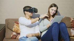 Άνδρας που χρησιμοποιεί τη συσκευή εικονικής πραγματικότητας δακτυλογραφώντας γυναικών στην ψηφιακή ταμπλέτα απόθεμα βίντεο