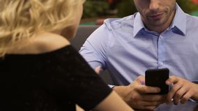 Άνδρας που χρησιμοποιεί το κινητό τηλέφωνο στον πίνακα ενώ γυναίκα που μιλά σε τον, ενόχληση, κρίση απόθεμα βίντεο