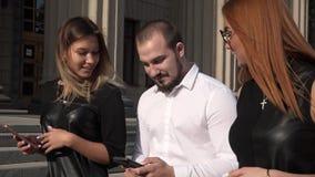Άνδρας σπουδαστής και δύο γυναίκες σπουδαστές πηγαίνουν κοντά στο πανεπιστήμιο και επικοινωνούν ο ένας με τον άλλον HD απόθεμα βίντεο