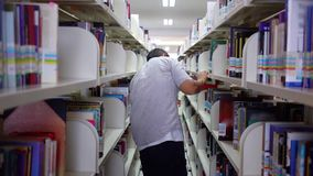 Άνδρας σπουδαστής που επιδιώκει το βιβλίο στο ράφι βιβλιοθηκών απόθεμα βίντεο
