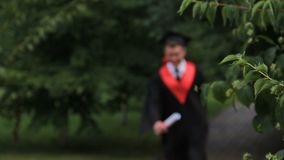 Άνδρας σπουδαστής στο ακαδημαϊκό φόρεμα που περπατά και που πηδά με τη χαρά στο πάρκο, βαθμολόγηση απόθεμα βίντεο
