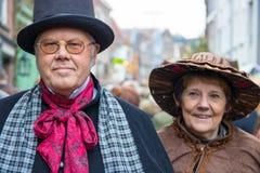 Άνδρας φεστιβάλ Dickens με τα γυαλιά και γυναίκα με τα κάλαντα Χριστουγέννων καπέλων Στοκ φωτογραφίες με δικαίωμα ελεύθερης χρήσης