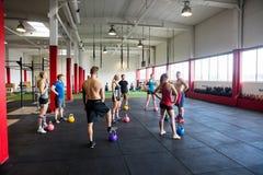 Άνδρες και γυναίκες με Kettlebells που στέκονται στη γυμναστική στοκ εικόνες