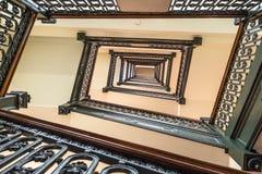 Άνεμος σκάλα με το ξύλινο κιγκλίδωμα ραμπών και σιδήρου στοκ εικόνες
