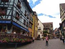 Άνετα εστιατόρια που διακοσμούνται με τα λουλούδια και τα σπίτια με τις ζωηρόχρωμες προσόψεις στις οδούς Riquewihr στοκ φωτογραφίες