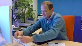 Άνετα ντυμένος γραφικός σχεδιαστής που εργάζεται σε έναν υπολογιστή φιλμ μικρού μήκους
