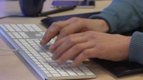 Άνετα ντυμένος γραφικός σχεδιαστής που εργάζεται σε έναν υπολογιστή απόθεμα βίντεο