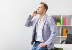 Άνετα ντυμένος νέος επιχειρηματίας που μιλά στο τηλέφωνο στην αρχή Στοκ εικόνα με δικαίωμα ελεύθερης χρήσης
