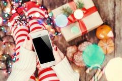 Άνετα Χριστούγεννα στο σπίτι Θηλυκά χέρια που κρατούν το κινητό τηλέφωνο Πόδια γυναικών ` s στις γυναικείες κάλτσες Χριστουγέννων Στοκ Φωτογραφίες