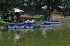 Άνετη γωνία για τη θερινή χαλάρωση με τον ξύλινους πάκτωνα και τη βάρκα στη λίμνη Ariana, gradina Borisova πάρκων Στοκ φωτογραφία με δικαίωμα ελεύθερης χρήσης