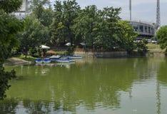Άνετη γωνία για τη θερινή χαλάρωση με τον ξύλινους πάκτωνα και τη βάρκα στη λίμνη Ariana, gradina Borisova πάρκων Στοκ εικόνες με δικαίωμα ελεύθερης χρήσης