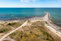 Άνετη παραλία της θάλασσας της Βαλτικής με τους βράχους και το πράσινο vegetat Στοκ Φωτογραφίες
