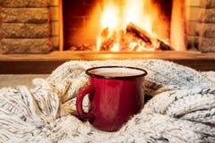 Άνετη σκηνή κοντά στην εστία με μια κόκκινη σμαλτωμένη κούπα με το καυτό τσάι και το άνετο θερμό μαντίλι στοκ εικόνα με δικαίωμα ελεύθερης χρήσης