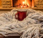 Άνετη σκηνή κοντά στην εστία με μια κόκκινη σμαλτωμένη κούπα με το καυτό τσάι και το άνετο θερμό μαντίλι στοκ φωτογραφίες