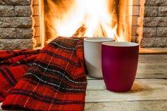 Άνετη σκηνή κοντά στην εστία με τα φλυτζάνια του καυτού τσαγιού και του άνετου θερμού μαντίλι στοκ εικόνες με δικαίωμα ελεύθερης χρήσης