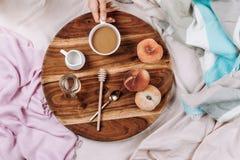 Άνετος φθινόπωρο ή χειμώνας flatlay του ξύλινου δίσκου με το φλιτζάνι του καφέ, ροδάκινα, κορφολόγος με το γάλα εγκαταστάσεων στοκ εικόνα με δικαίωμα ελεύθερης χρήσης