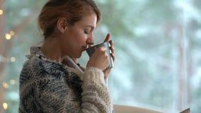 Άνετος χειμερινός τρόπος ζωής Νέο ευτυχές φλιτζάνι του καφέ κατανάλωσης γυναικών που φορά το πλεκτό σπίτι συνεδρίασης πουλόβερ απ απόθεμα βίντεο