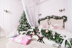 Άνετο εγχώριο εσωτερικό Χριστουγέννων νέο έτος διακοσμήσεων φωτεινό δωμάτιο κρεβατοκάμαρων με το μεγάλο διπλό κρεβάτι Στοκ Εικόνες