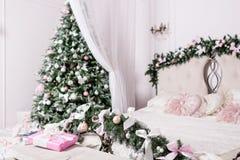 Άνετο εγχώριο εσωτερικό Χριστουγέννων νέο έτος διακοσμήσεων φωτεινό δωμάτιο κρεβατοκάμαρων με το μεγάλο διπλό κρεβάτι Στοκ Φωτογραφίες