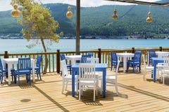 Άνετο ελληνικό εστιατόριο με τις άσπρες καρέκλες και τους μπλε πίνακες Στοκ Εικόνα