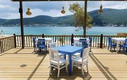 Άνετο ελληνικό εστιατόριο με τις άσπρες καρέκλες και τους μπλε πίνακες Στοκ εικόνες με δικαίωμα ελεύθερης χρήσης
