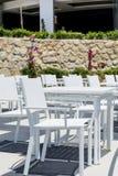 Άνετο ελληνικό εστιατόριο με τις άσπρους καρέκλες και τους πίνακες Στοκ Εικόνα