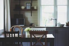 Άνετο θερινό πρωί στην αγροτική κουζίνα εξοχικών σπιτιών Ξύλινος πίνακας με την ανθοδέσμη των φρέσκων λουλουδιών, ανοικτό να τοπο Στοκ εικόνες με δικαίωμα ελεύθερης χρήσης