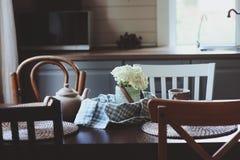 Άνετο θερινό πρωί στην αγροτική κουζίνα εξοχικών σπιτιών Τσάι, μπισκότα και ανθοδέσμη των φρέσκων λουλουδιών Στοκ Φωτογραφίες