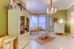 Άνετο πράσινο δωμάτιο κοριτσιών με τα λευκά γραφεία και τη ρόδινη κουβέρτα Στοκ Φωτογραφία