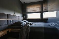 Άνετο, σκοτεινό εσωτερικό κρεβατοκάμαρων με τα γκρίζα φύλλα και κάλυμμα και ένα φ στοκ φωτογραφίες