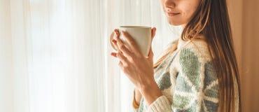 άνετο σπίτι Γυναίκα με το φλυτζάνι του ζεστού ποτού από το παράθυρο Η εξέταση το παράθυρο και πίνει το τσάι καλημέρα με το τσάι Χ στοκ εικόνες