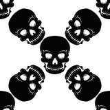 Άνευ ραφής μαύρα κρανία σχεδίων σε ένα υπόβαθρο Στοκ Φωτογραφίες