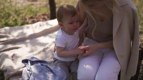 Άνθος κερασιών Sakura - νέα συνεδρίαση μητέρων mom με το γιο μωρών μικρών παιδιών της σε ένα πάρκο στη Ρήγα, Λετονία Ευρώπη φιλμ μικρού μήκους