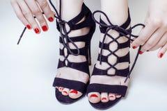 Άνθρωποι έννοιας μόδας: γυναίκα με τα κόκκινα δένοντας κορδόνια pedicure μανικιούρ καρφιών στα παπούτσια τακουνιών ύψους που απομ Στοκ εικόνες με δικαίωμα ελεύθερης χρήσης