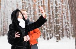 Άνθρωποι, έννοια εποχής, αγάπης, τεχνολογίας και ελεύθερου χρόνου - ευτυχές ζεύγος που παίρνει την εικόνα με το smartphone κατά τ Στοκ Φωτογραφία