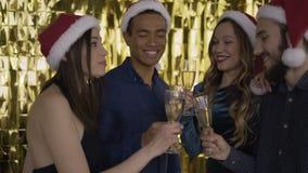 4 άνθρωποι ανθρώπων που μιλούν σε μια γιορτή Χριστουγέννων τύποι και στα κόκκινα καπέλα Άγιος Βασίλης μικτοί άνθρωποι φυλών χρυσό φιλμ μικρού μήκους