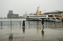 Άνθρωποι αποβαθρών ατμοπλοίων της Ιστανμπούλ που περπατούν στη βροχή Στοκ Εικόνες