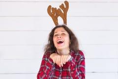 Άνθρωποι, διακοπές και έννοια Χριστουγέννων - αστείο κορίτσι santa στα κέρατα ελαφιών στο κεφάλι της στο άσπρο υπόβαθρο στοκ εικόνες